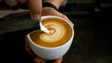 Kellner erstellt eine Figur im Milchschaum des Kaffee's