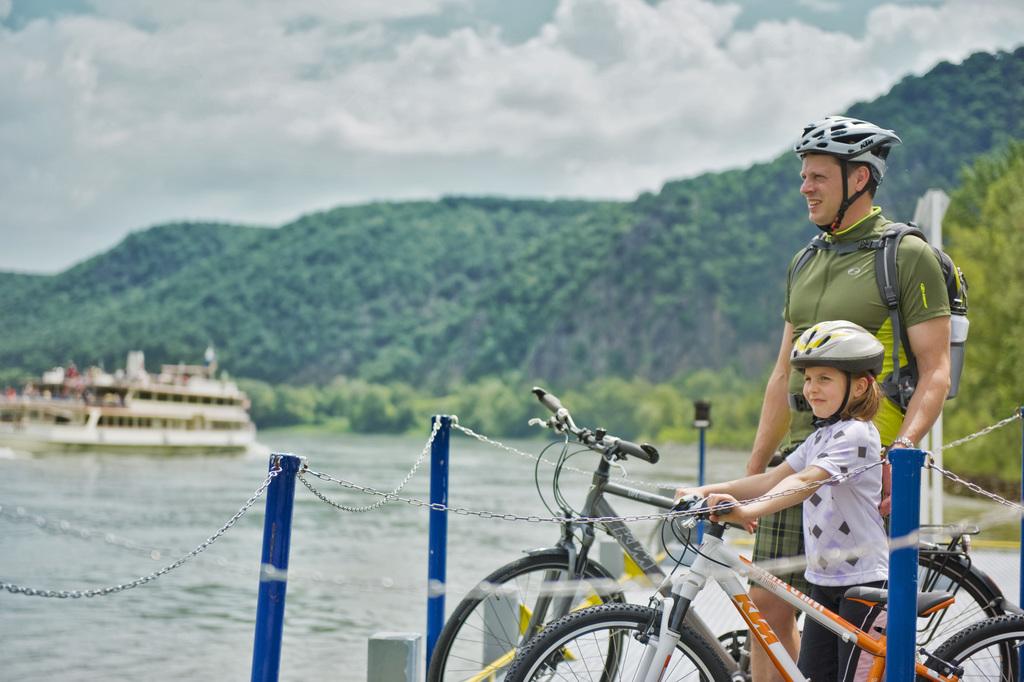 Familie beim Radfahren auf dem Donauradweg mit Blick auf ein Schiff