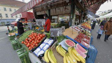 Obst und Gemüsestände und Besucher des Naschmarktes.