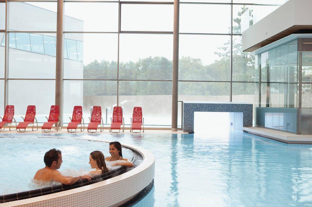 drei Personen sitzen im Whirlpool im Innenbereich