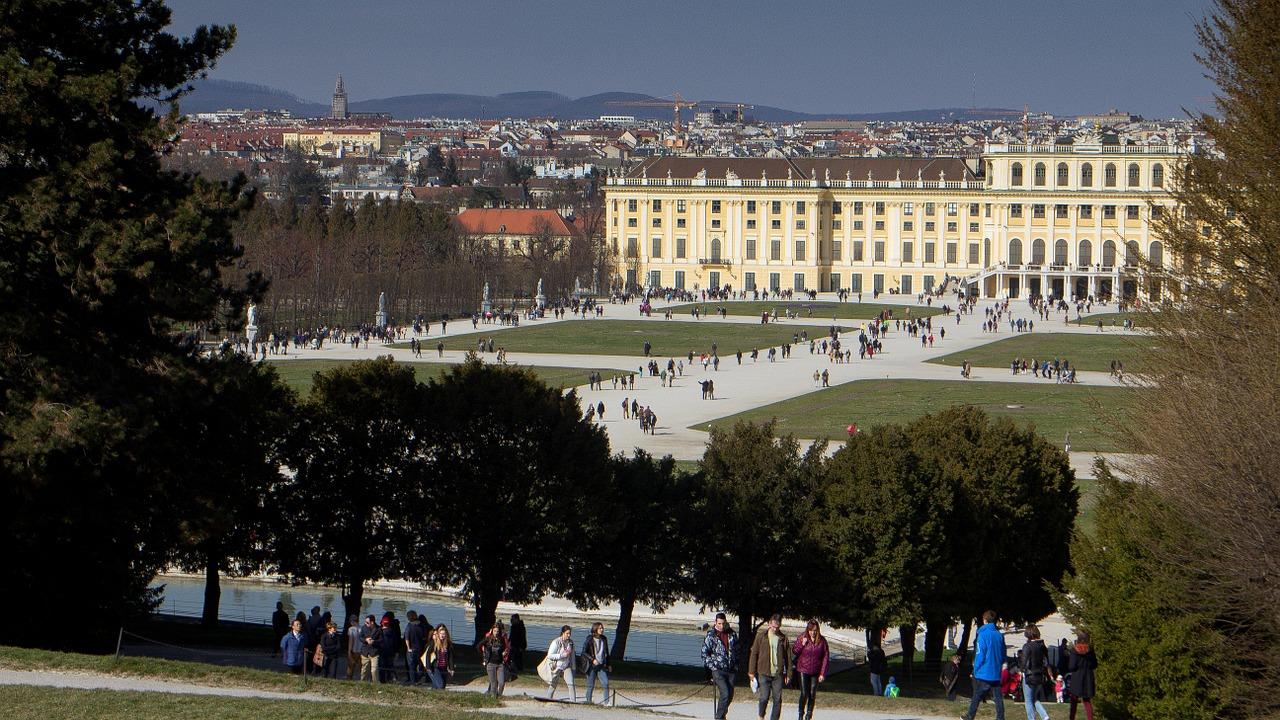 Ein Blick in den Schlosspark, viele Menschen gehen spazieren im grünen Park