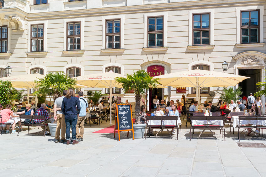 people on outdoor terrace of hofburg cafe in inner castle court in der burg in downtown vienna, austria