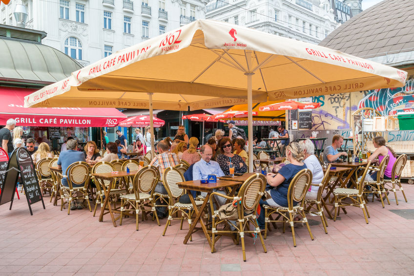 people having drinks on outdoor terrace of cafe on naschmarkt in vienna, austria