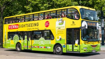tourists on hop on hop off bus of yellow line sightseeing inner city of vienna, austria