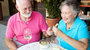 senior couple on a date enjoys an artichoke dip appetizer