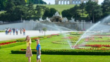 children in schönbrunn palace garden and gloriette on hill top