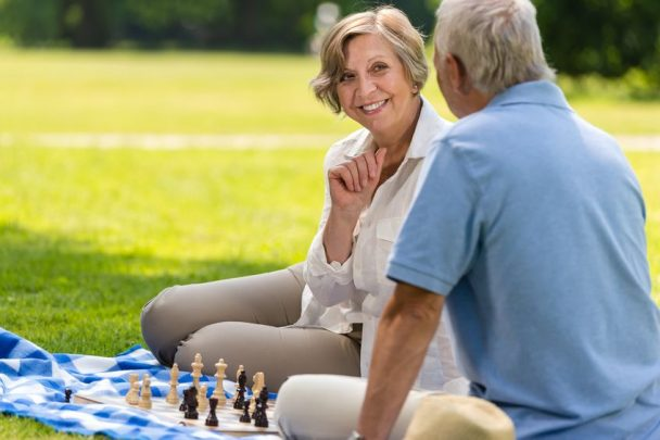 senior wife and husband playing chess on blanket summer park