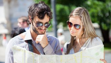 couple of young tourists reading a map