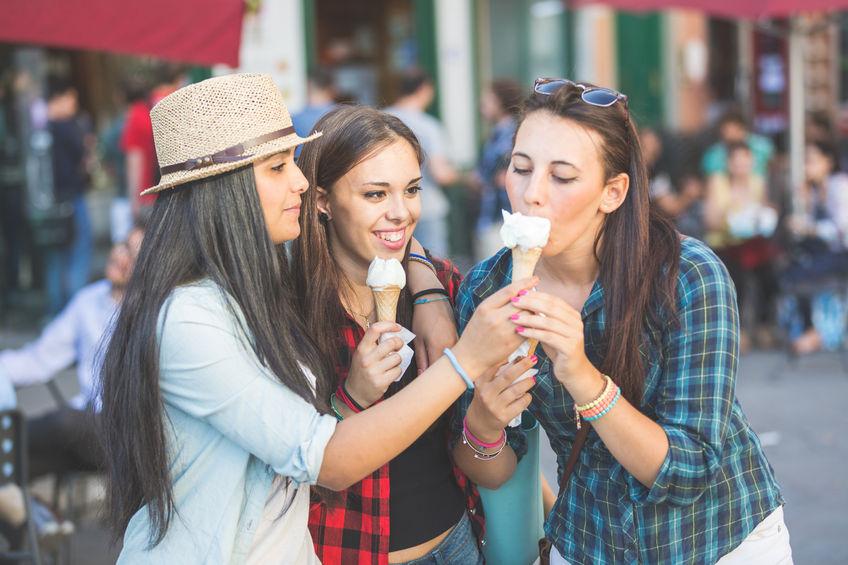 three happy women eating ice cream in the city