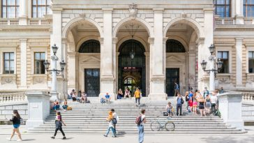 people at entrance of main building of university on ringstrasse in inner city of vienna