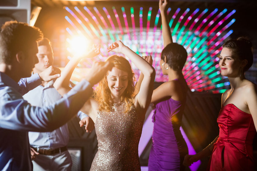 group of smiling friends dancing on dance floor in bar