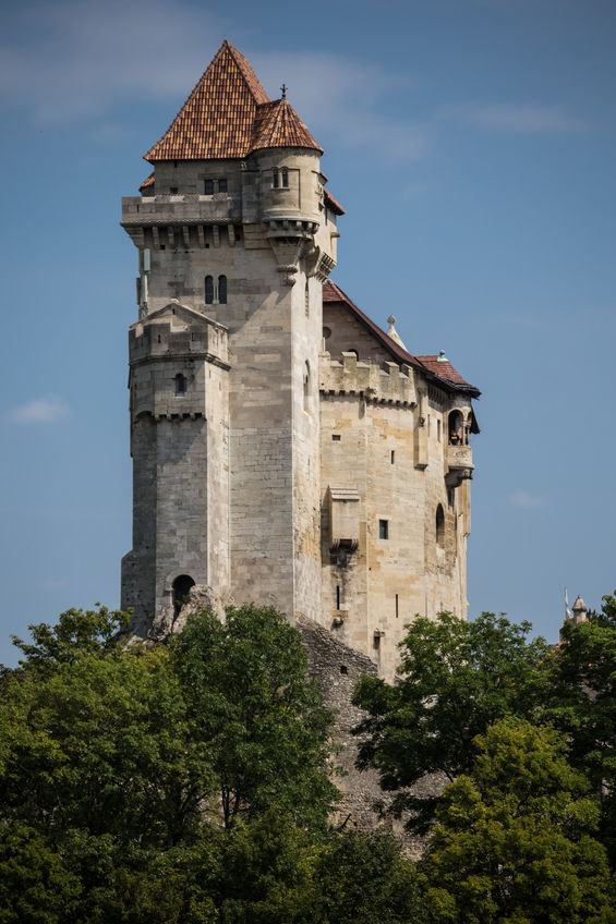 ancient castle liechtenstein, vienna woods, village maria enzersdorf, austria - against bright blue sky and green forest
