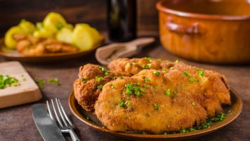 Wiener Schnitzel with potatoes and herbs on top