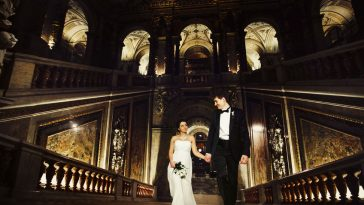 bride looks at a groom going upstairs in an old hall of vienna theatre