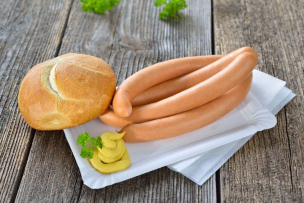 four wieners with a fresh roll and spicy mustard on a paper plate