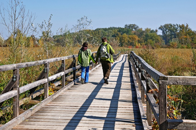 Ein Pärchen mit Wanderausrüstung schreitet über einen Holzbrücke