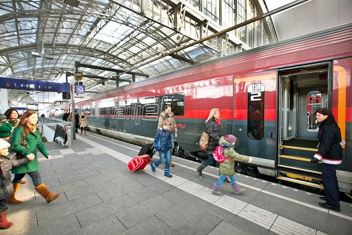 Eine Familie steigt in den Zug am Bahnhof ein
