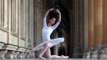 Beautiful ballerina in white tutu dancing in a palace
