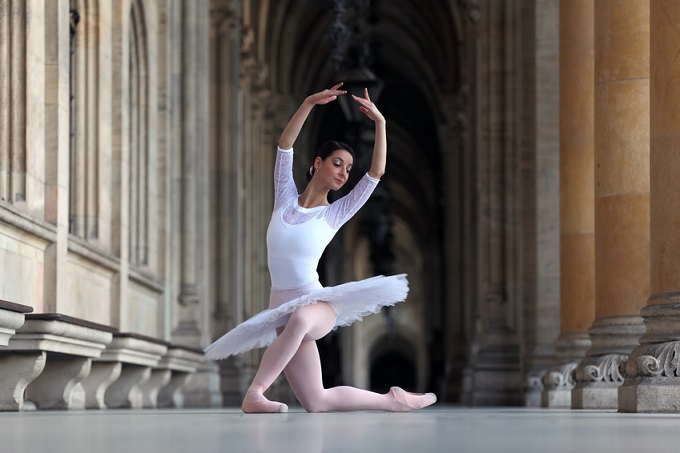 Beautiful ballerina in white tutu dancing in a palace