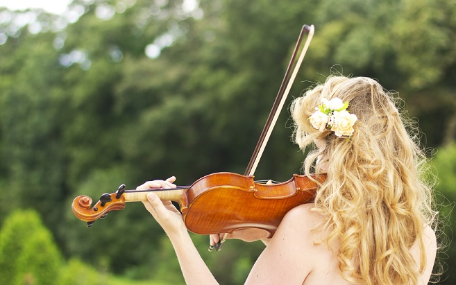 Beautiful smiling girl playing on the violin outdoors.