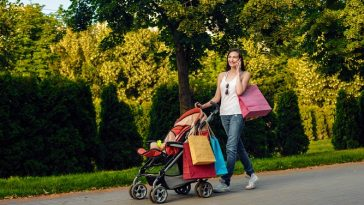 Young happy mother with baby carriage having walk