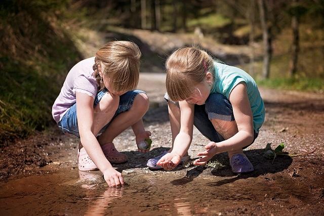 zwei Mädchen spielen mit Wasserlacke