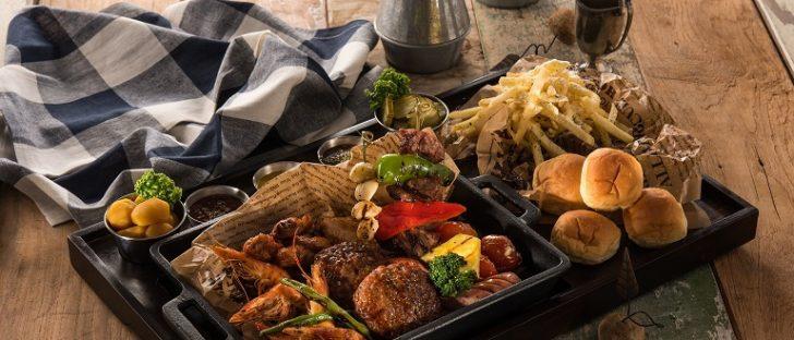 BBQ-Platte mit vielen gegrillten Köstlichkeiten und Brötchen