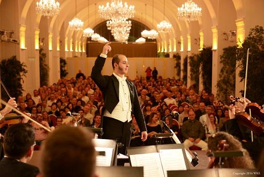 Blick von der Bühne über die Musiker und Dirigent hinweg auf die Zuseher in den Raum hinein.