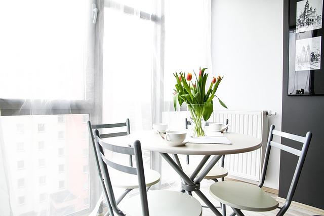 heller Raum mit Tisch und drei Stühlen inkl. Tulpen