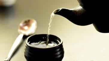 aus einer Keramikteekanne läuft Tee in eine Keramikschüssel