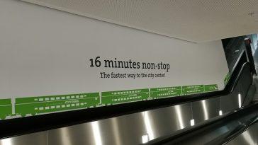 ein Schriftzug betreffend der Dauer der Fahrt in die Innenstadt, zu sehen entlang einer Rolltreppe.