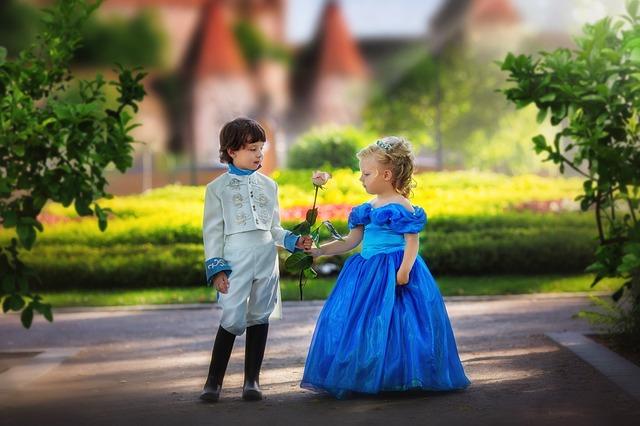 zwei Kinder verkleidet als Prinzessin und Prinz in einem Park.