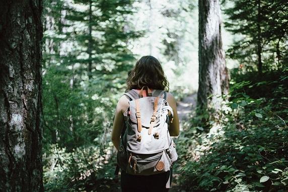 Wandernde Frau auf einem Weg durch den Wald