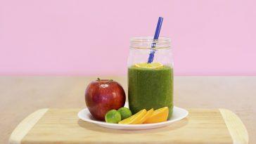 grüner Smoothie auf einem Teller, verziert mit einem Apfel und Orangenstücken.