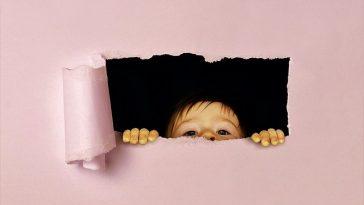 Kind sieht durch eine kleine Öffnung durch ein Blatt Papier