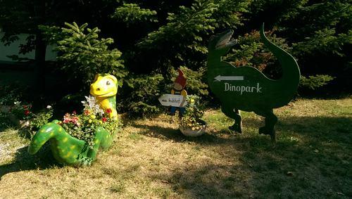Einganbsbereich des Familienpark mit kleinem Dino und Schild