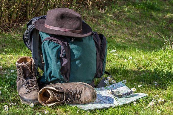 Ein Rucksack, Hut und Wanderschuhe liegen auf einer Wiese