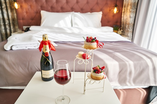 Blick auf ein wunderschönes Bett, im Vordergrund eine Flasche Champagner